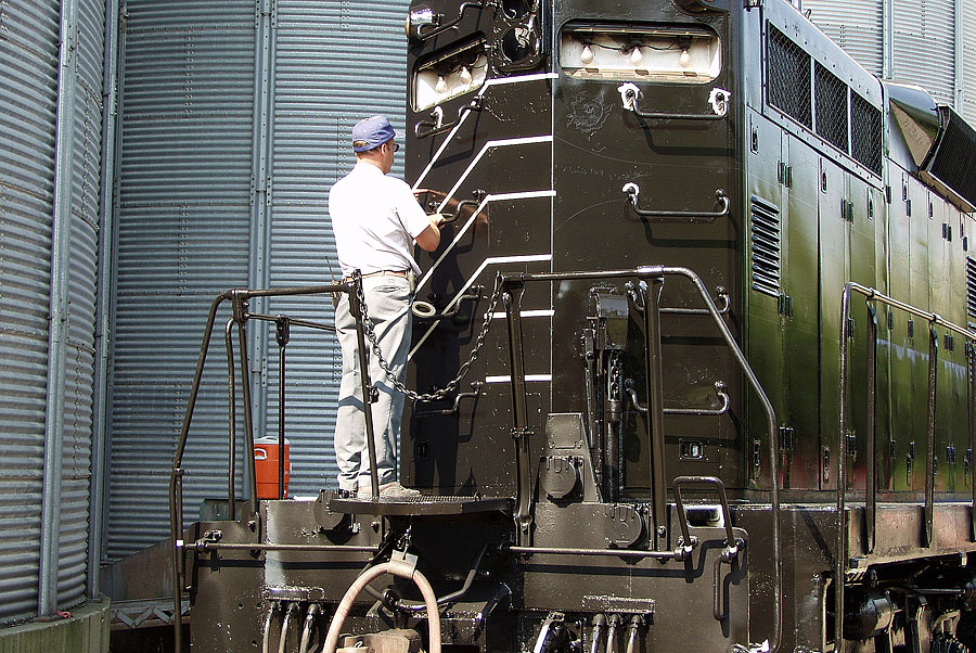 A locomotive is masked for striping during a restoration project.